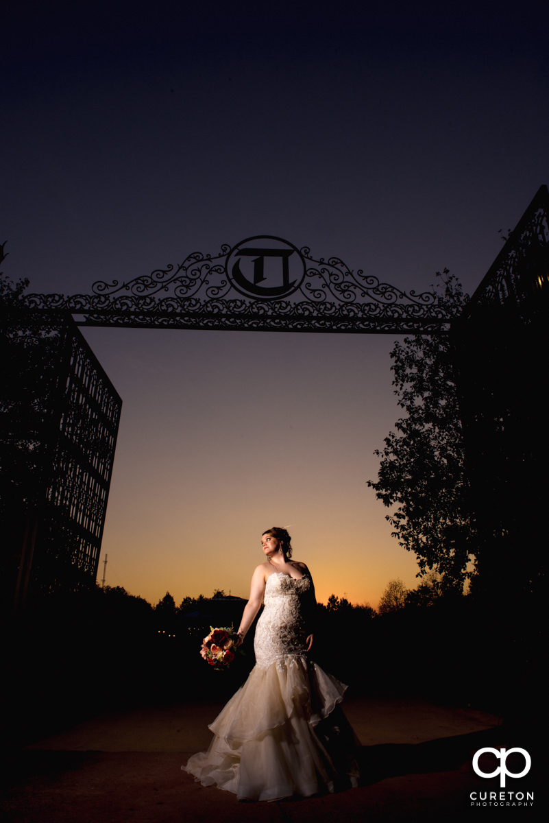 Bride standing in front of the gate at sunset at Edinburgh West before her wedding.