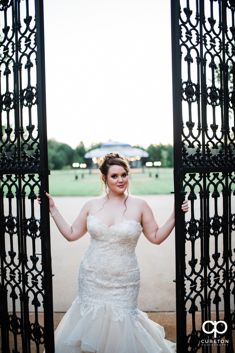 Bride holding on to an iron gate.