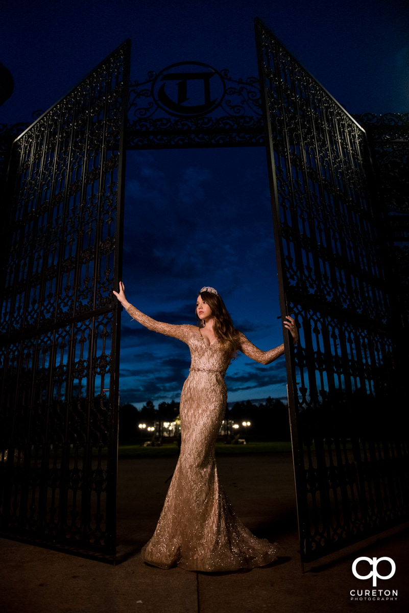 Bride holding onto an iron gate wearing a couture custom wedding dress at Edinburg West in Greenville,SC.