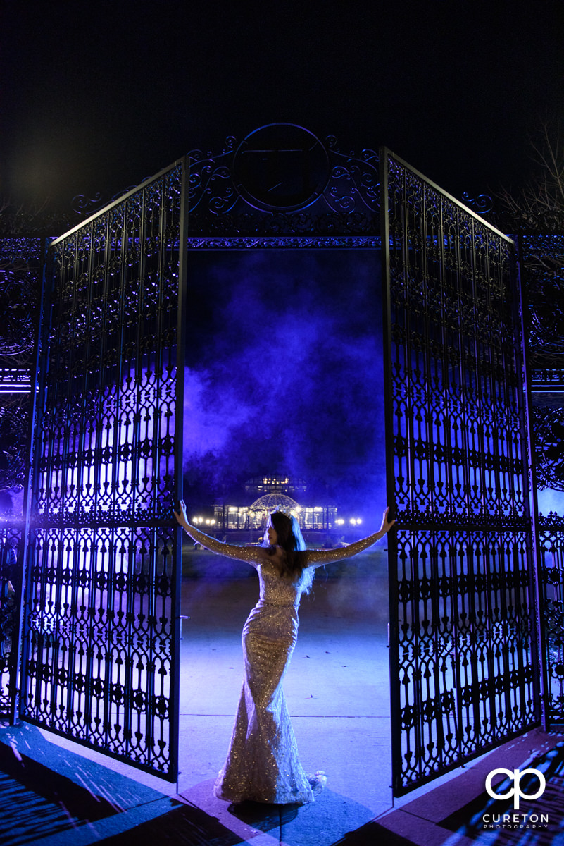 Bride in purple light at the iron gate entrance to Edinburgh West with the English conservatory in the background.