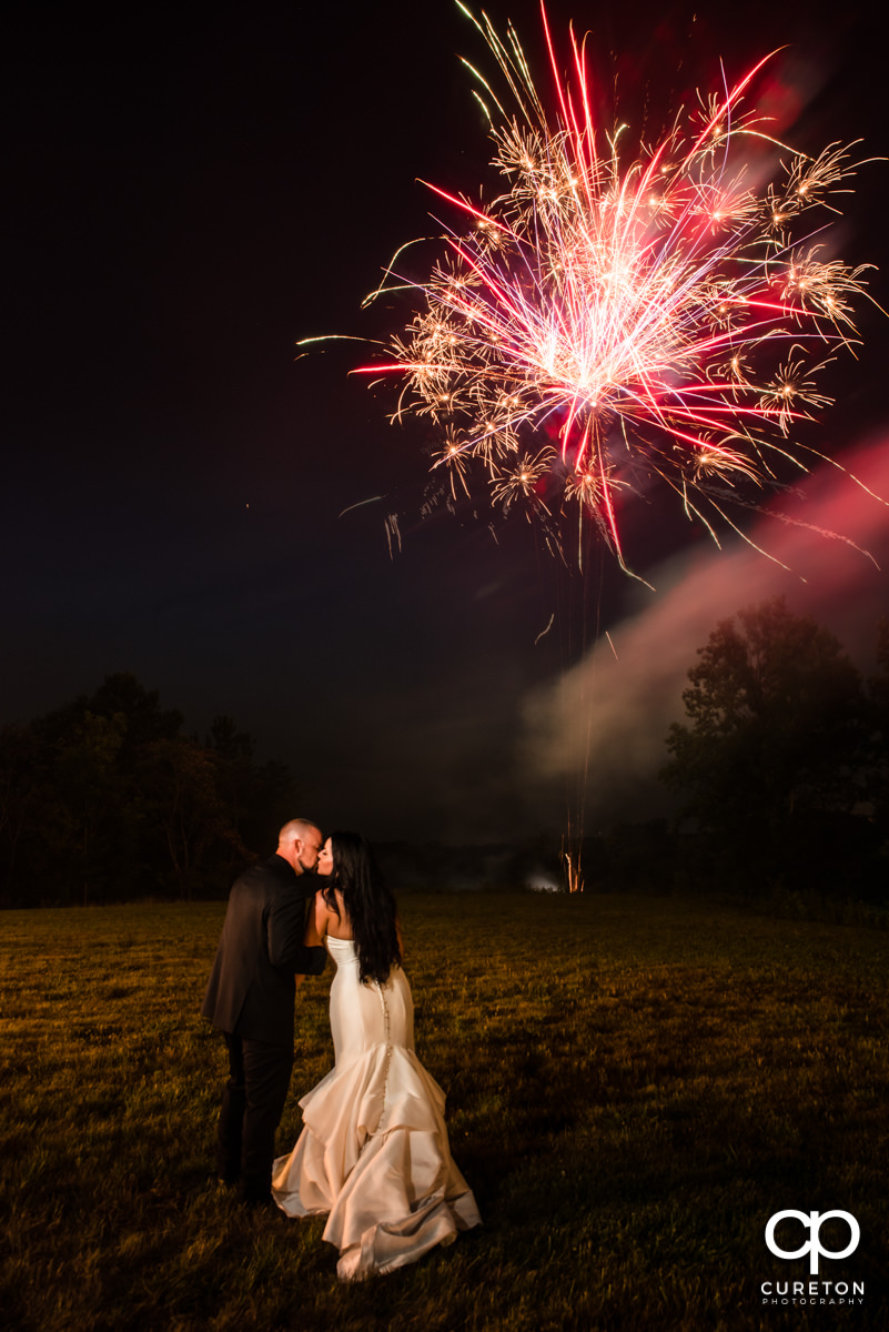 Bride and groom kissing after their wedding at Edinburgh West as fireworks light up the night sky.
