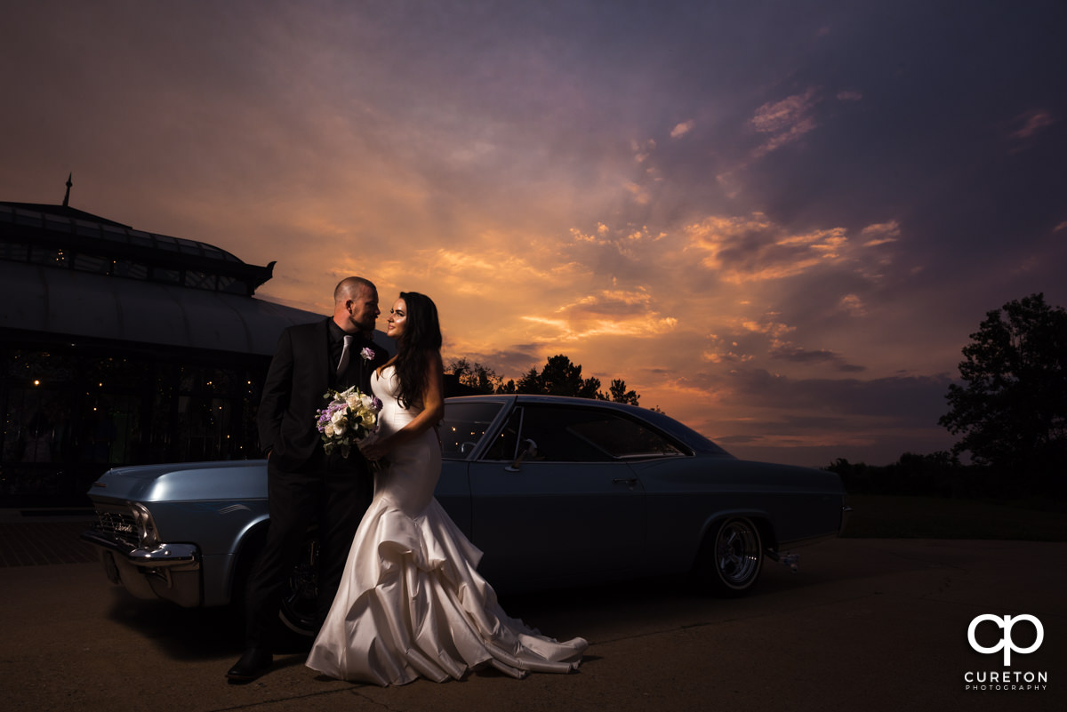 Groom and bride standing in front of a vintage car at thier Edinburgh West wedding in Taylors,SC.