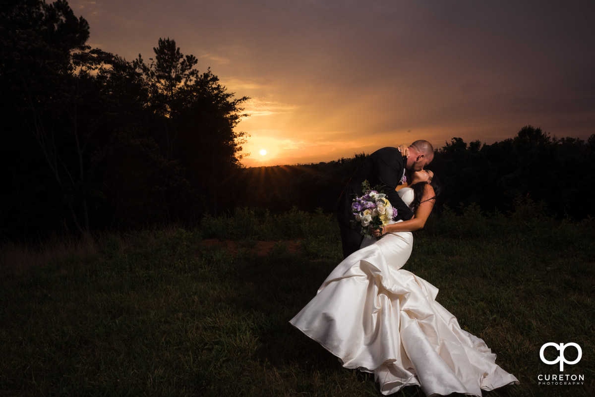 Groom dancing with his bride at sunset after their wedding at Edinburgh West in Taylors,SC.