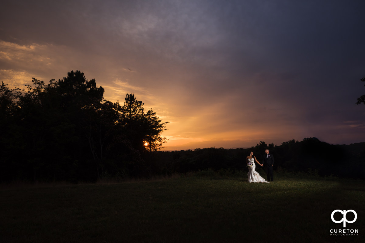 Bride and groom walking in a field at sunset at the Edinburgh West wedding venue.