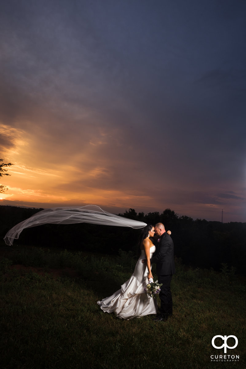 Bride's veil blowing in the wind at sunset.