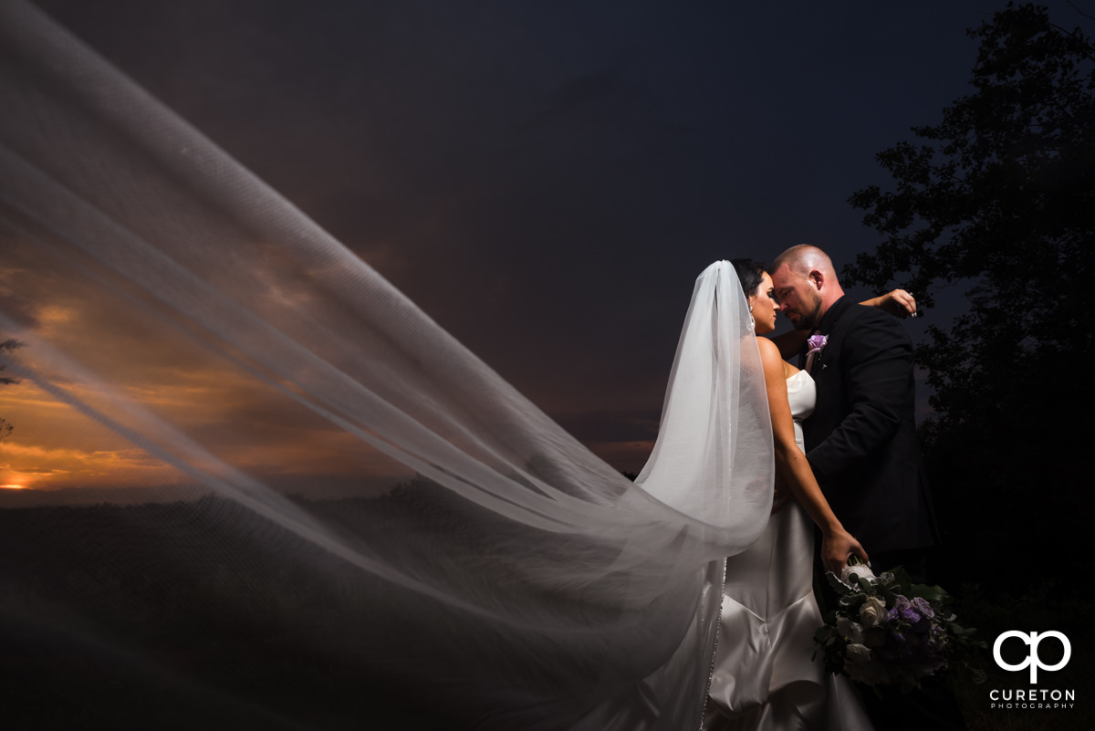 Bride's veil blowing into the wind as she hugs her groom at sunset.