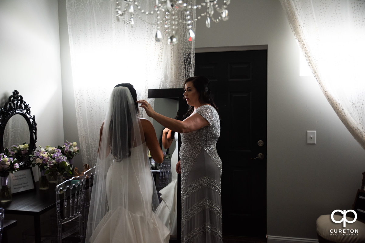 Mother of the bride helping her with her veil.