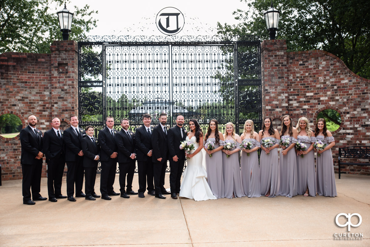 Wedding party in front of iron gates at Edinburgh West.