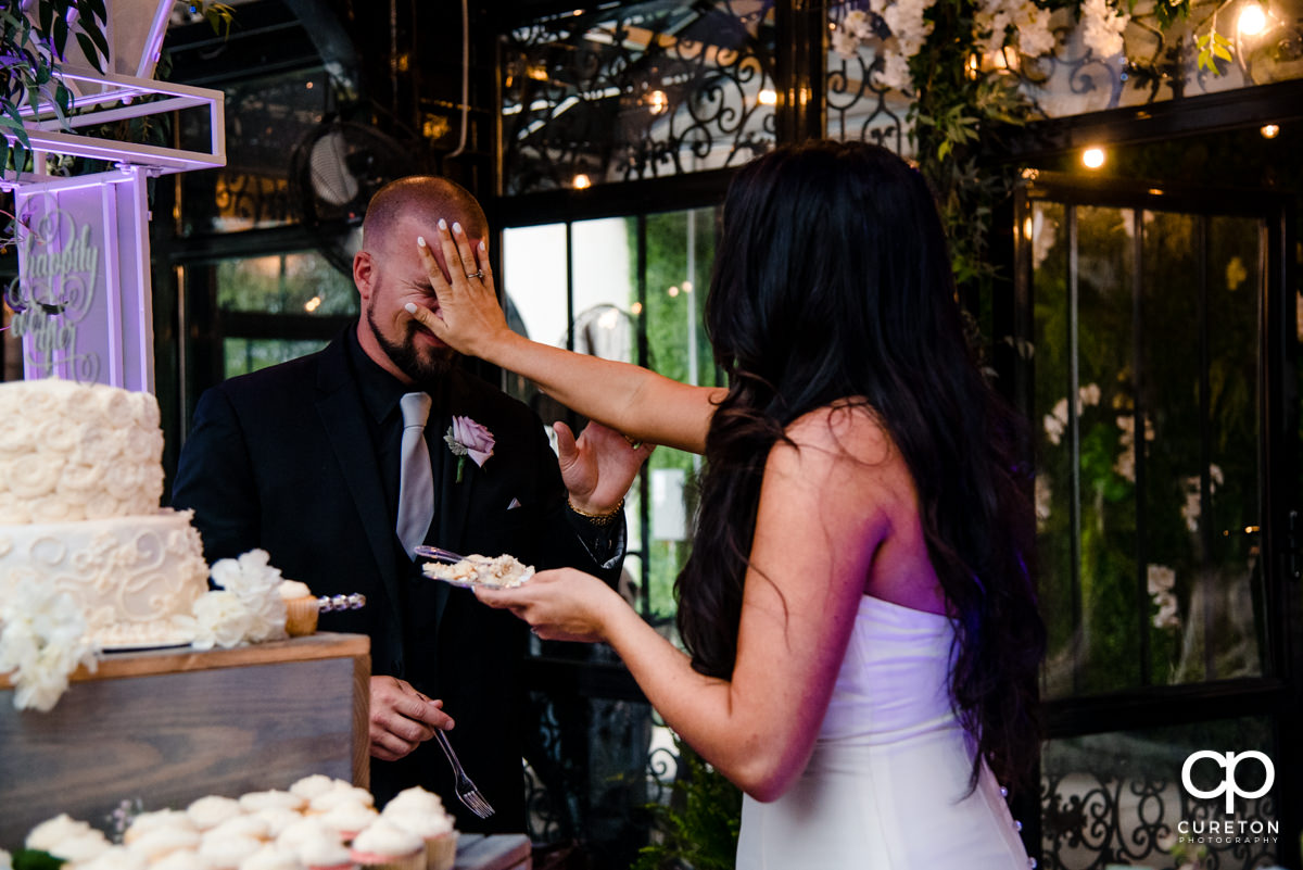 Bride smashing cake into the groom's face.