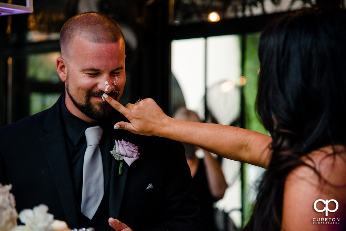 Bride smearing cake onto the groom's nose.