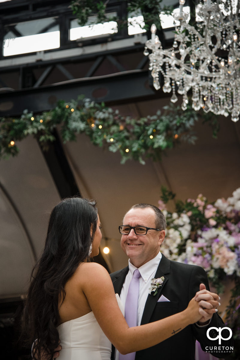 Bride's dad smiling while dancing with his daughter.