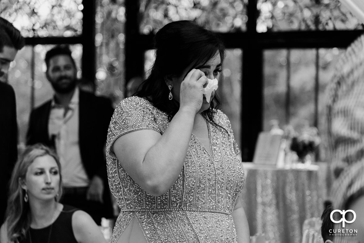 Bride's mom wiping away tears.