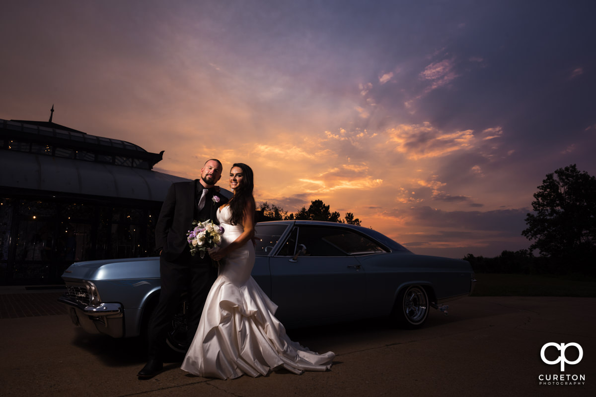 Bride and groom with the getaway car.