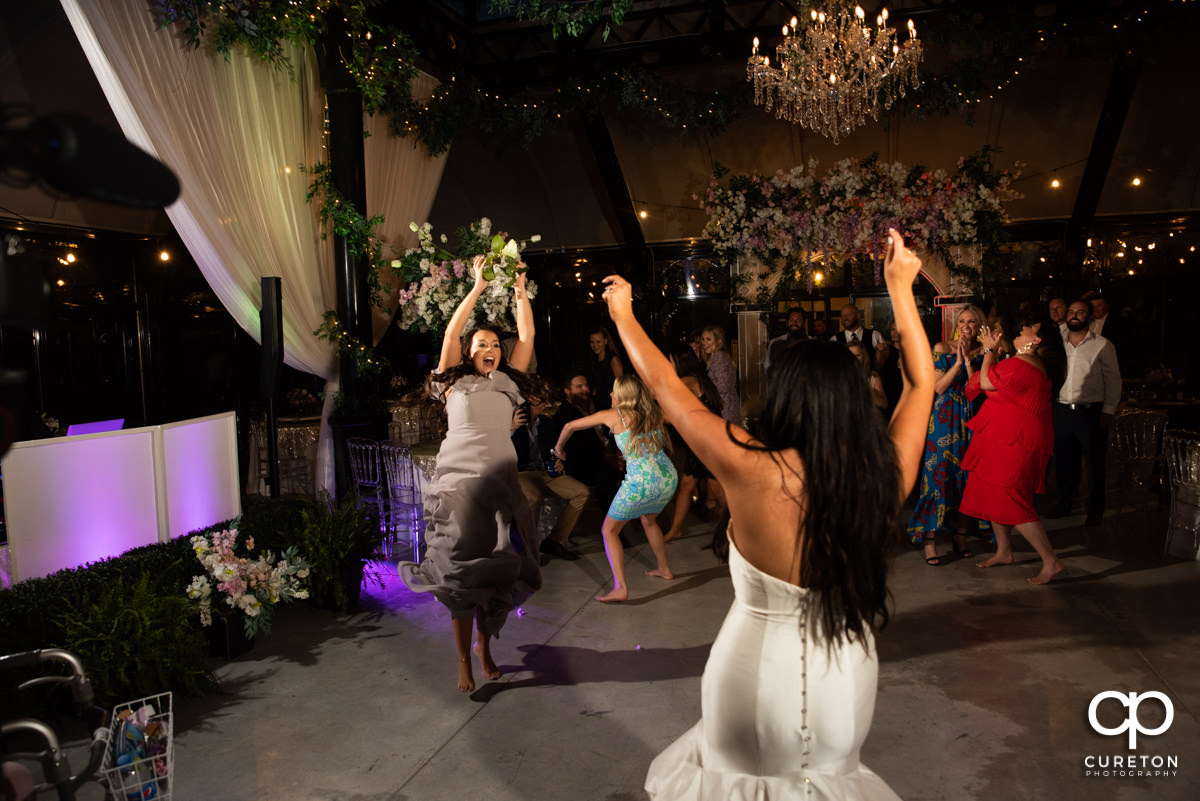 Bride tossing the bouquet to her bridesmaid.