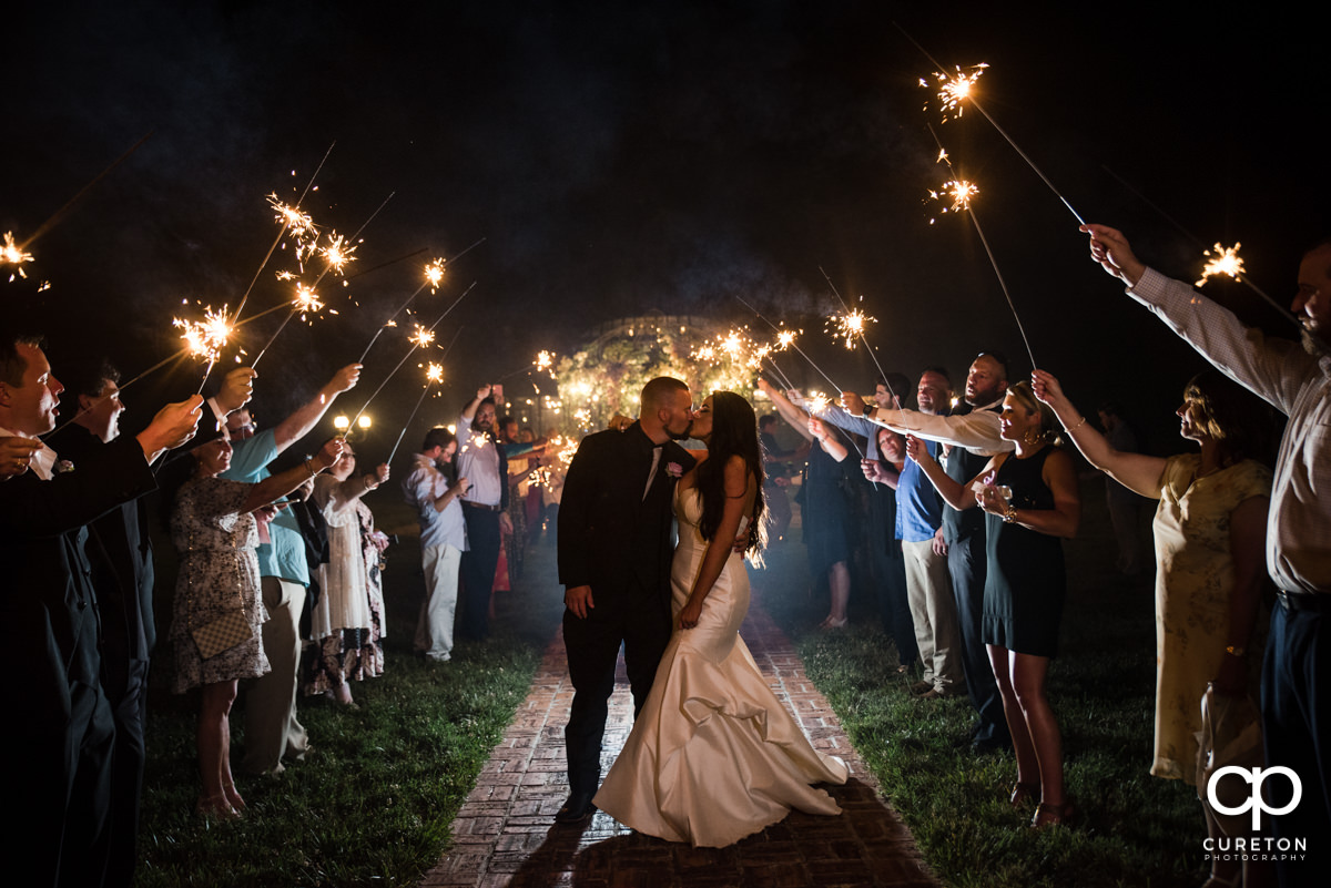 Bride and groom kissing as they leave through sparklers at Edinburgh West wedding venue.