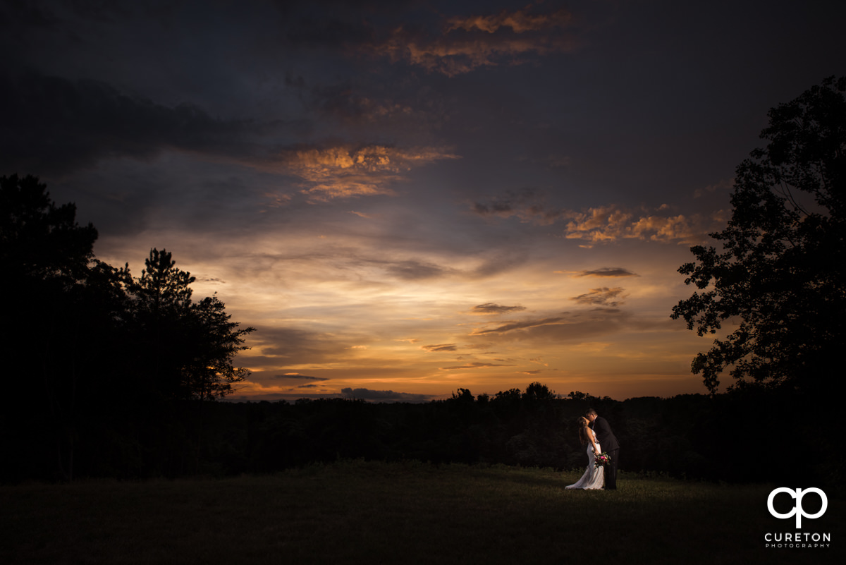 Bride and groom in a field during sunset at their Edinburgh West wedding.