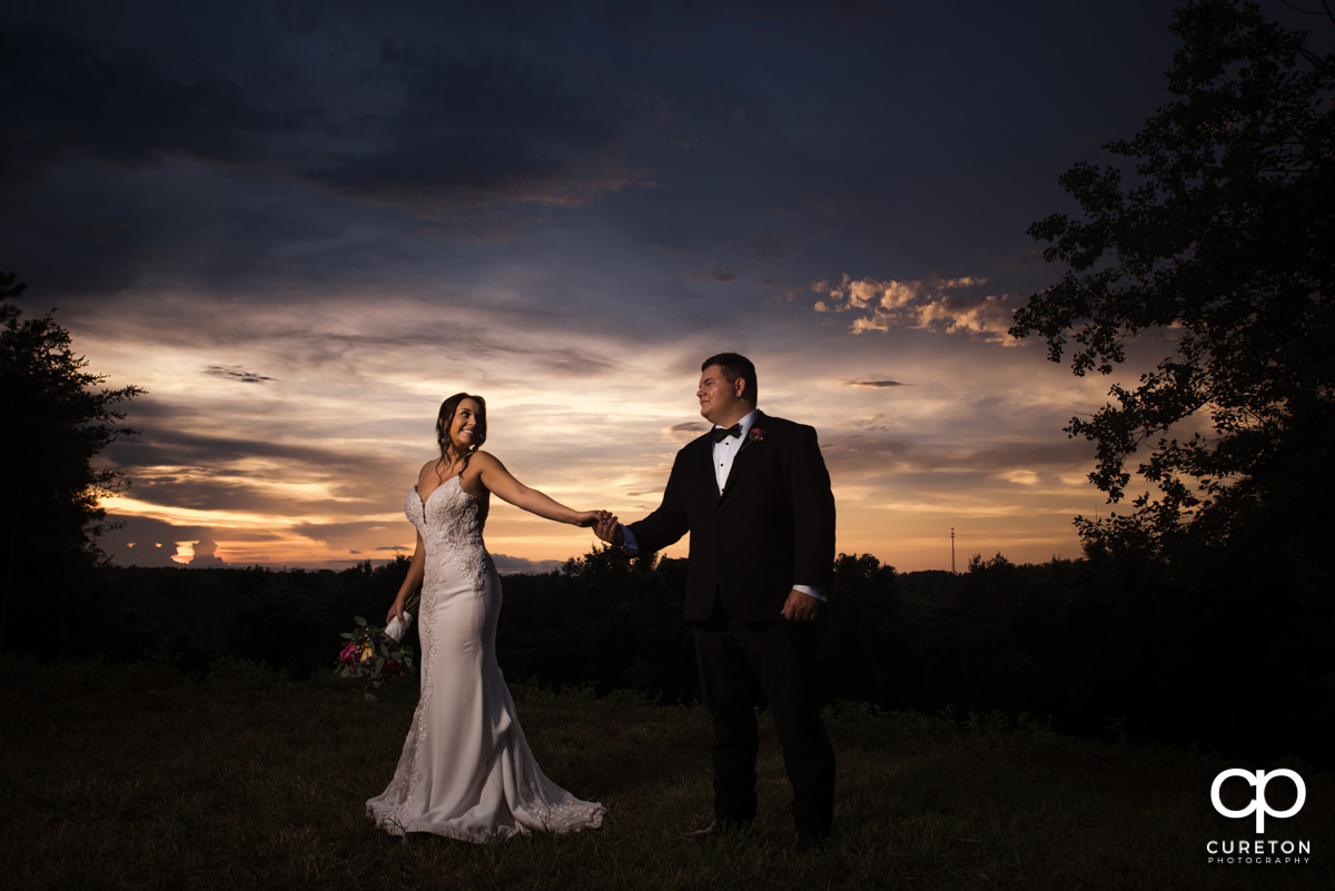 Bride leading her groom into a field at sunset.