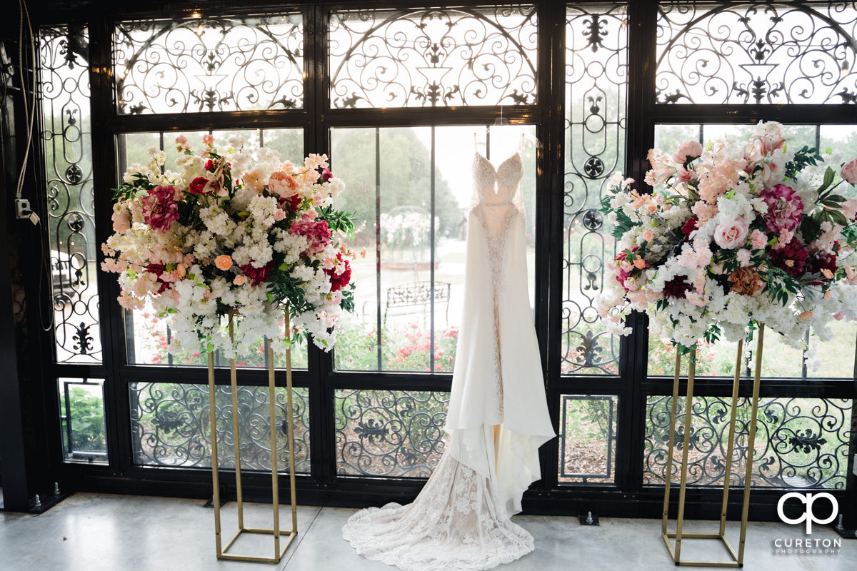 Bridal dress between two floral arrangements.