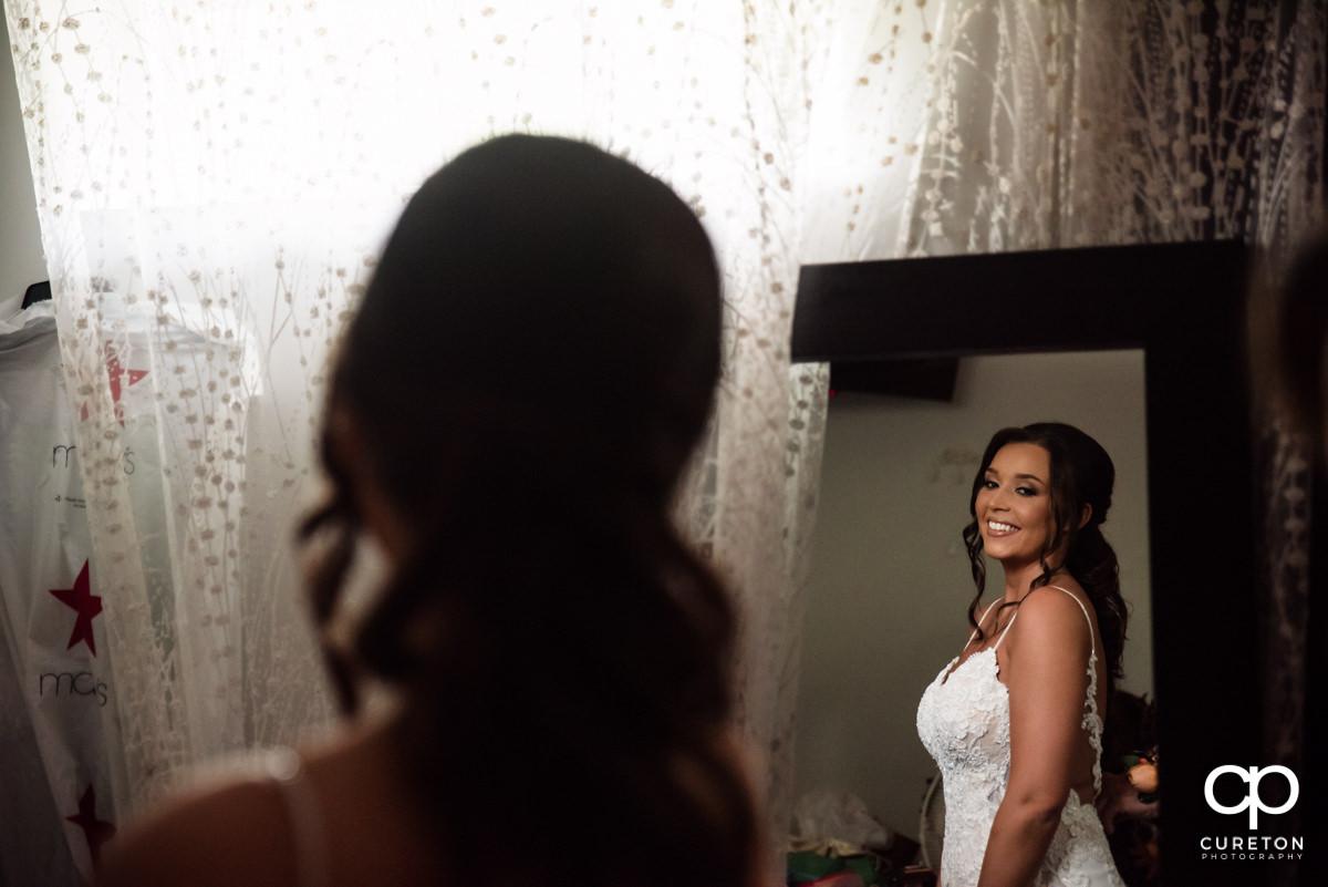 Bride looking into a mirror.