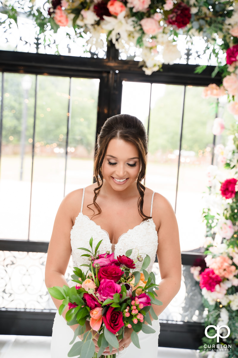 Bride smiling at her flowers.