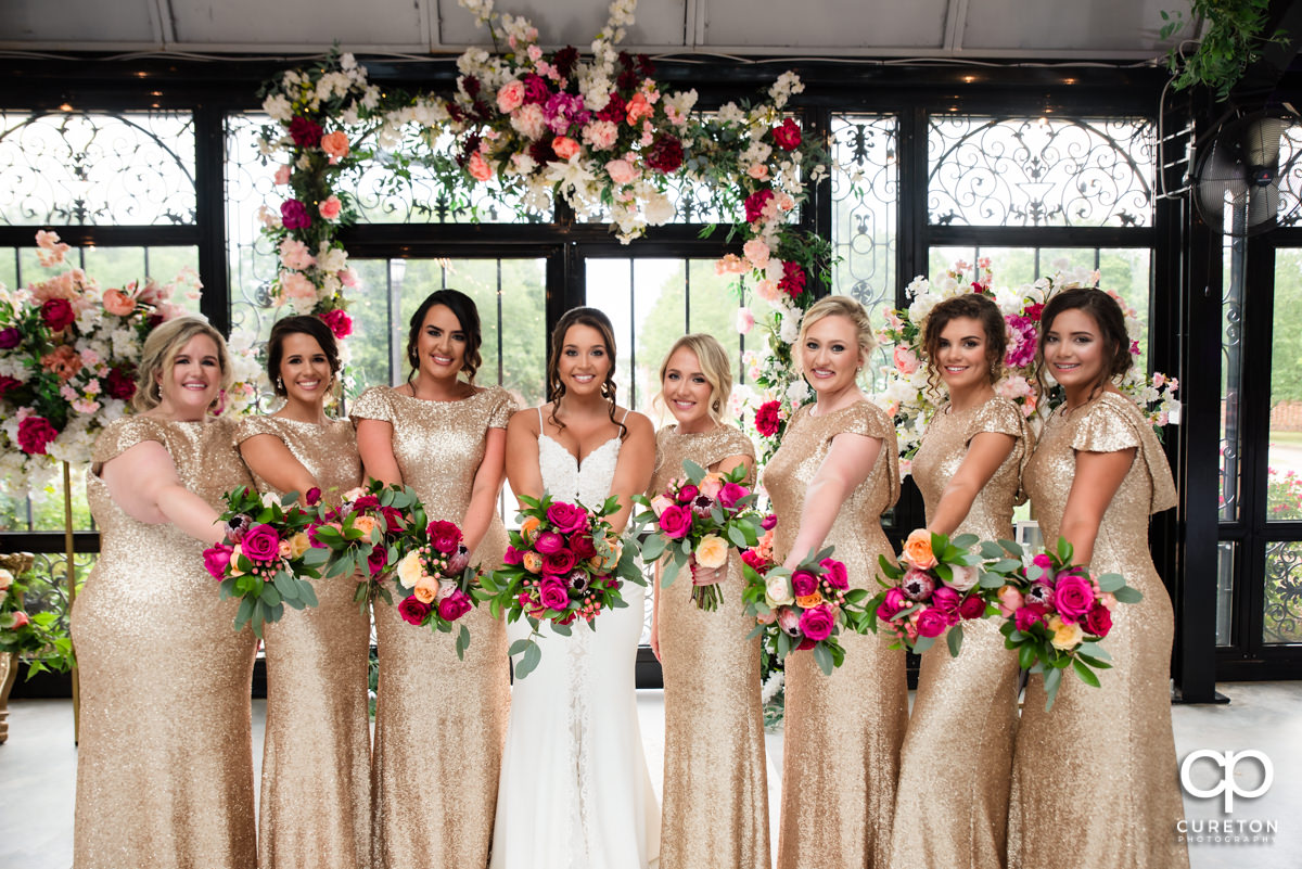 Bridesmaids in gold dresses holding flowers.