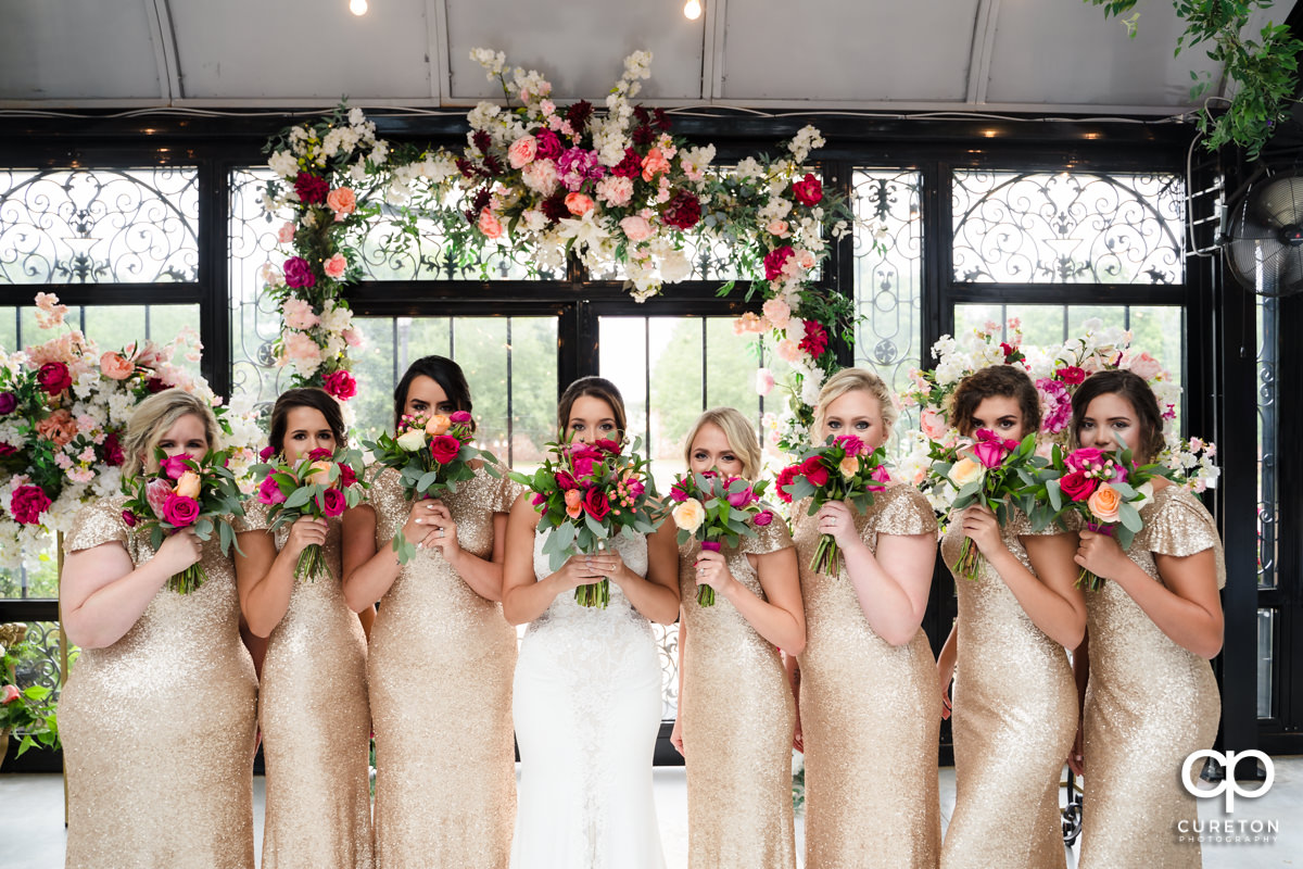 Bridesmaids holding flowers up to their face.