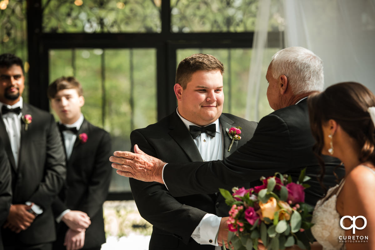 Groom shaking grandfather's hand.