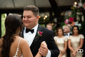 Groom smiling while dancing with the bride.