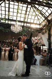 Groom kissing his bride while dancing.