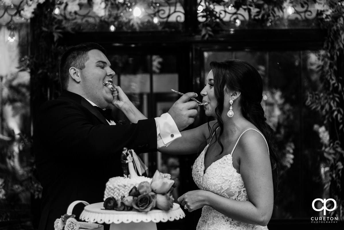 Bride feeding cake to the groom.