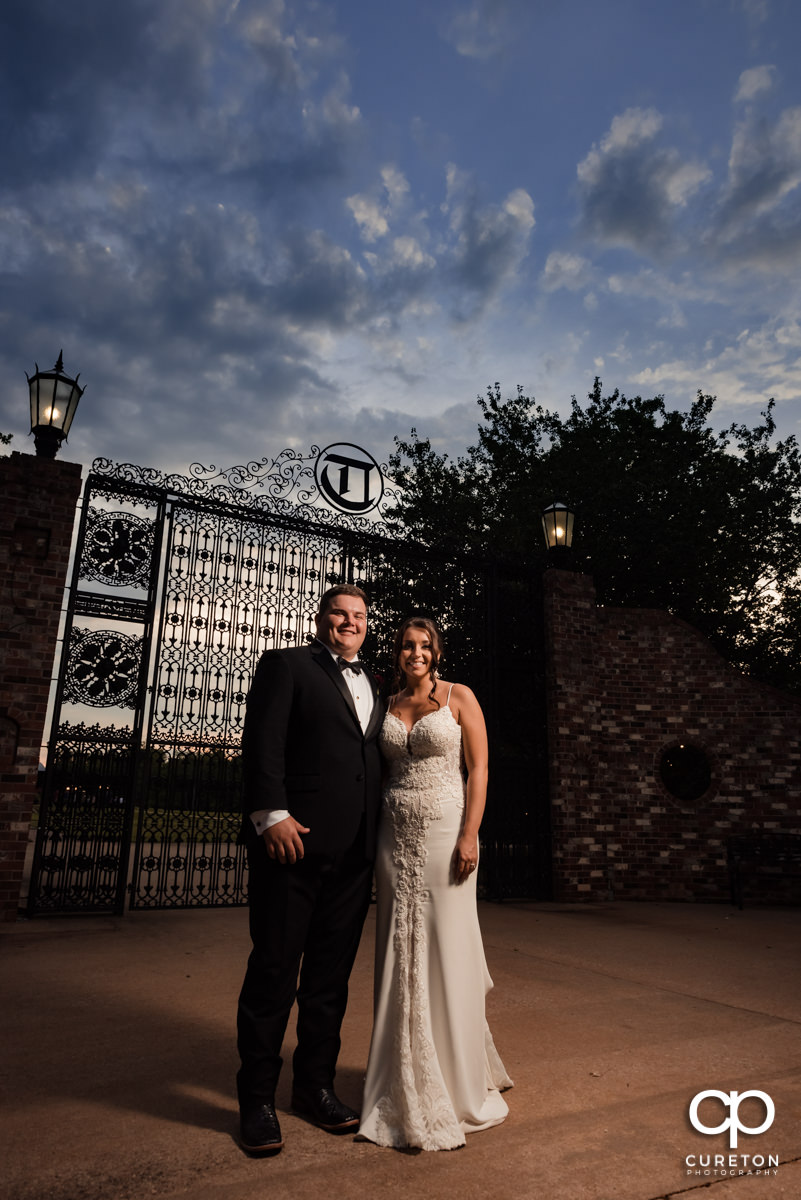 Bride and groom in front of iron gates.