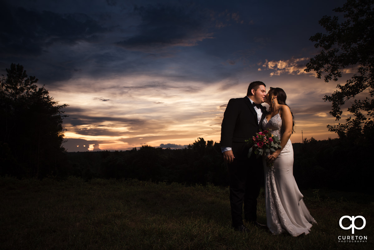 Bride and groom kissing in a field at sunset.