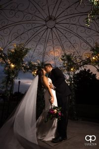 Groom dipping his bride at sunset in the gazebo at Edinburgh West.