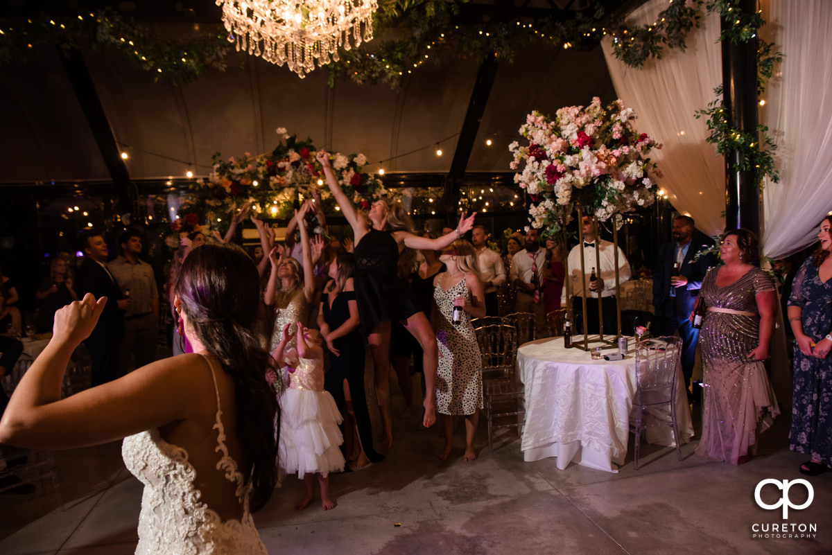 Guests jumping to catch the bride's bouquet.