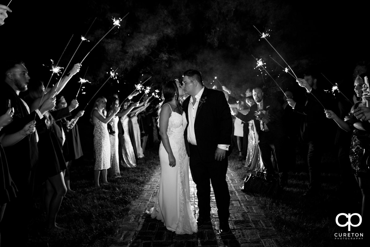 Bride and groom kissing under sparklers.