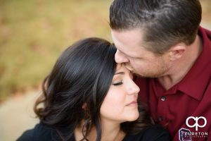 Groom kissing his bride on the forehead during their engagement session at Furman university.