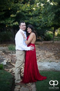 Groom with his future bride wearing a bright red dress during their engagement session.