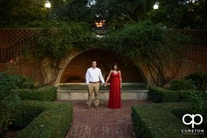 Bride and groom holding hands in the Rose Garden at Furman university.