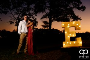 Bride and groom with a lit letter of their initial.