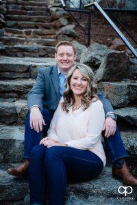 Engaged couple sitting on some stone steps.