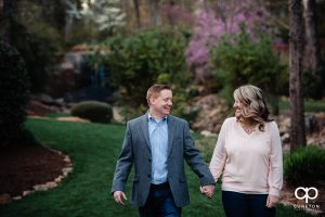 Engaged couple walking in the Rock Quarry Garden in Greenville.