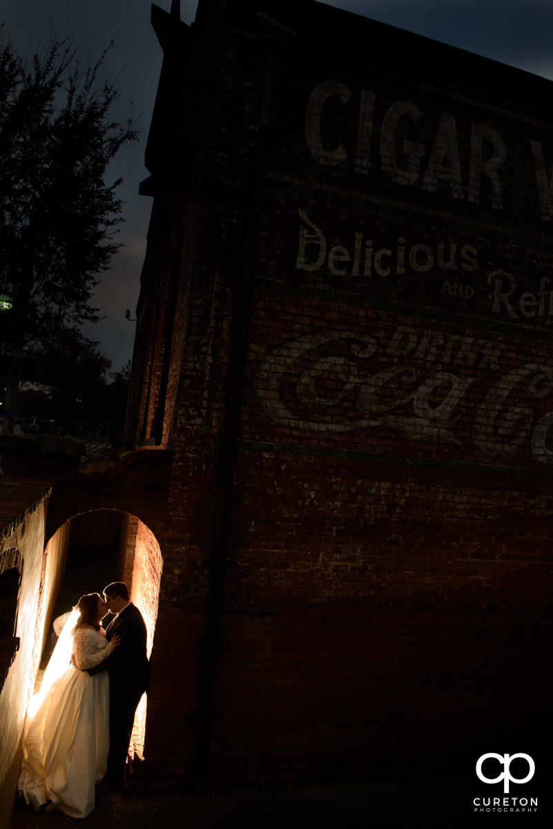 Bride and groom standing in an archway at twilight during their fall wedding at the Old Cigar Warehouse in downtown Greenville,SC.