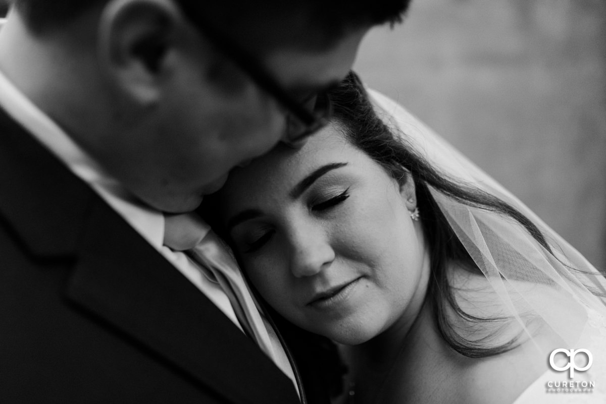 Bride laying her head on her groom's chest and closing her eyes.