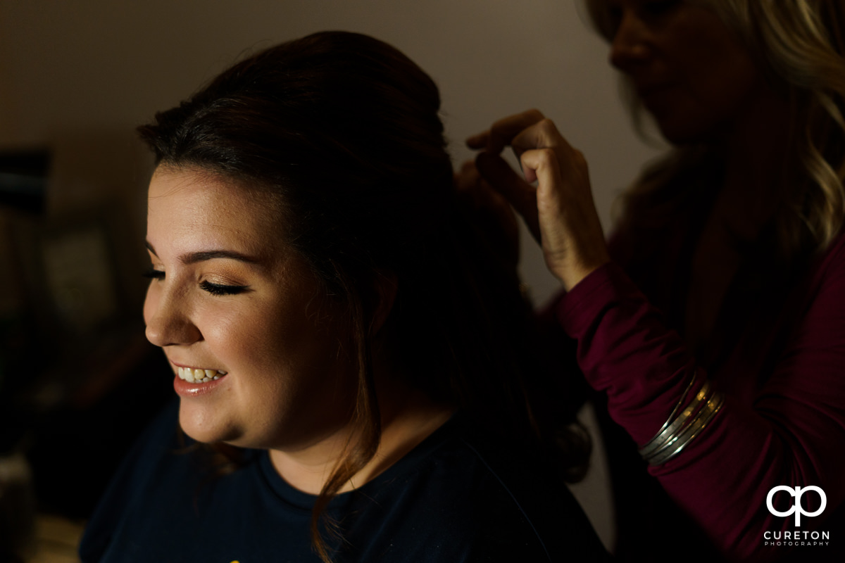 The bride having her hair and makeup done before the wedding ceremony.