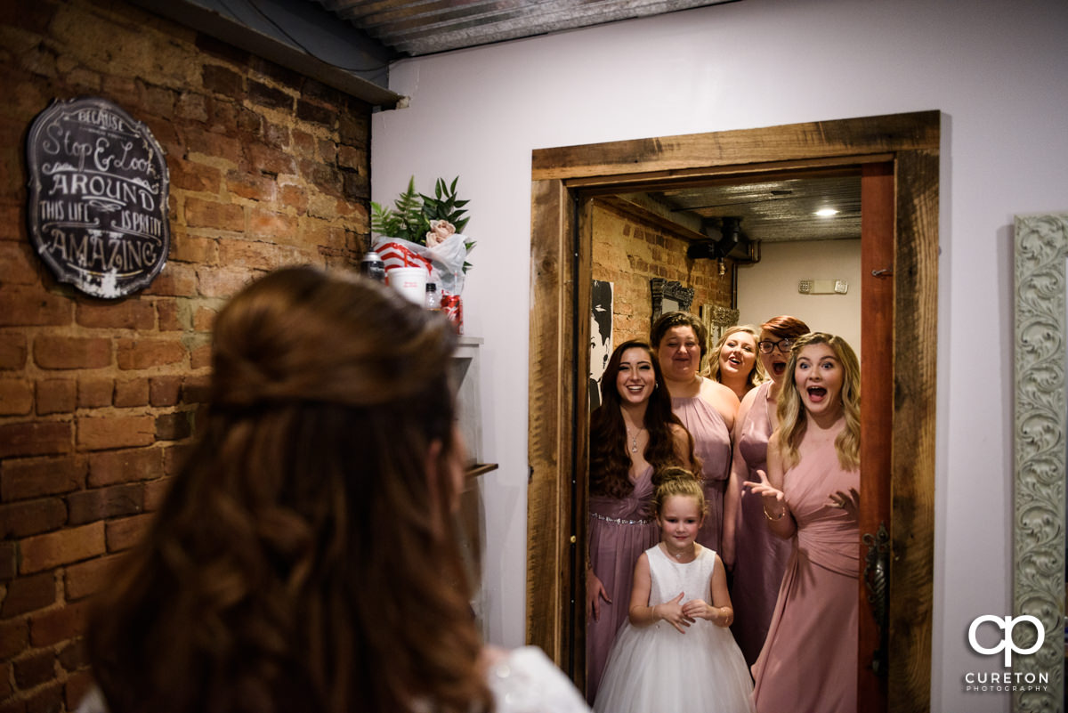 Bridesmaids seeing the bride in her dress for the first time in the bridal suite during their fall wedding at the Old Cigar Warehouse in downtown Greenville,SC.