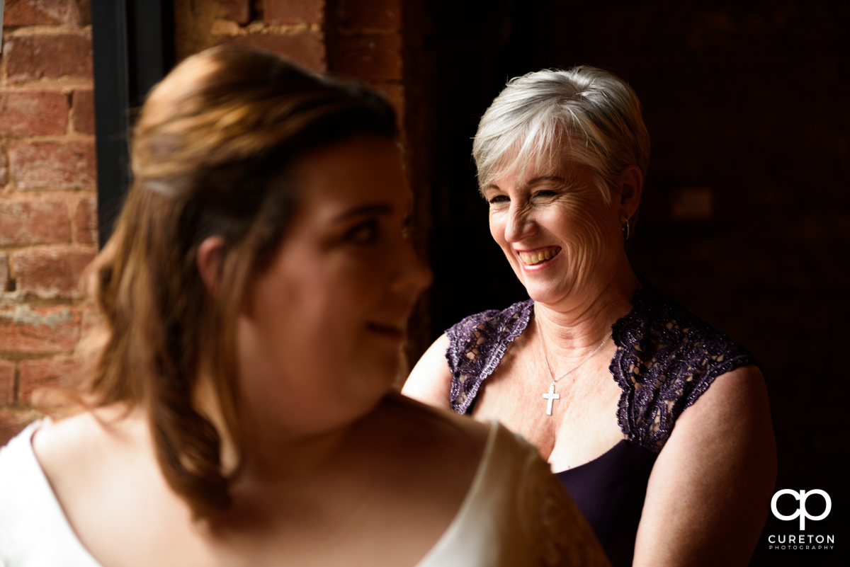 Bride's mother smiling while helping her into her dress.
