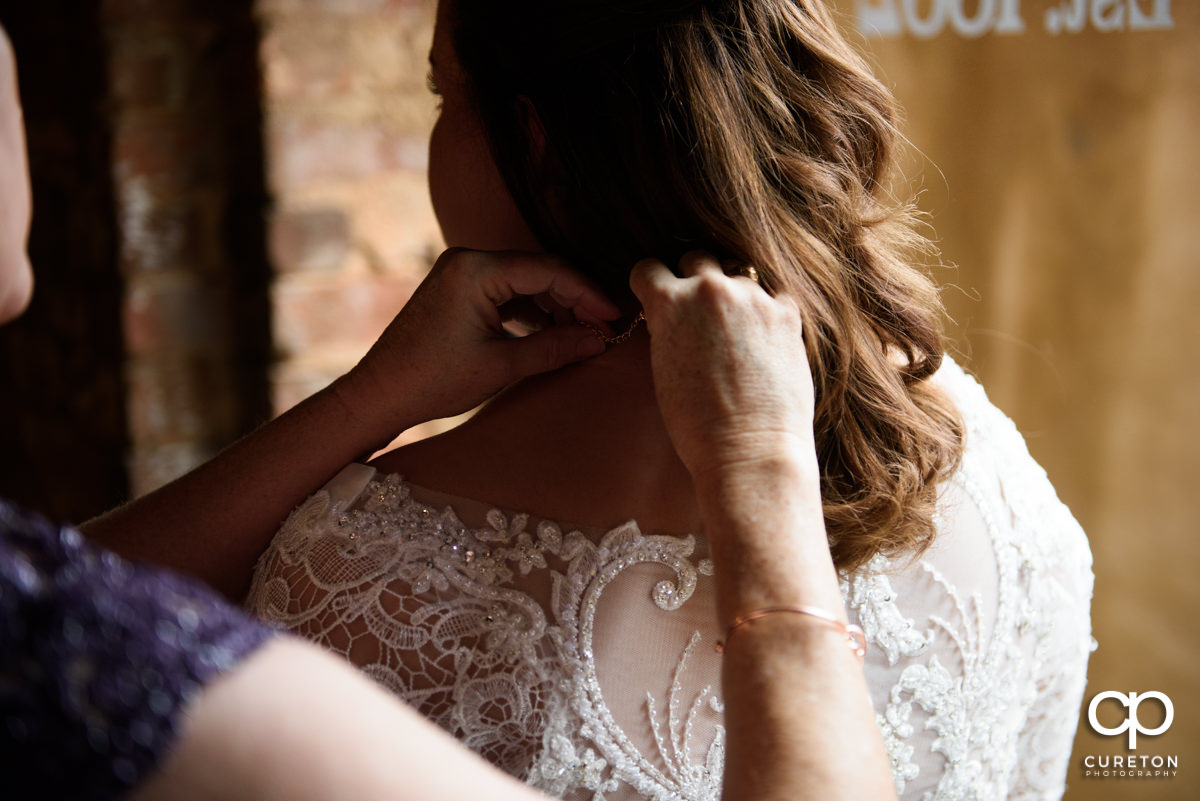 Bride's mother putting a necklace on her daughter.