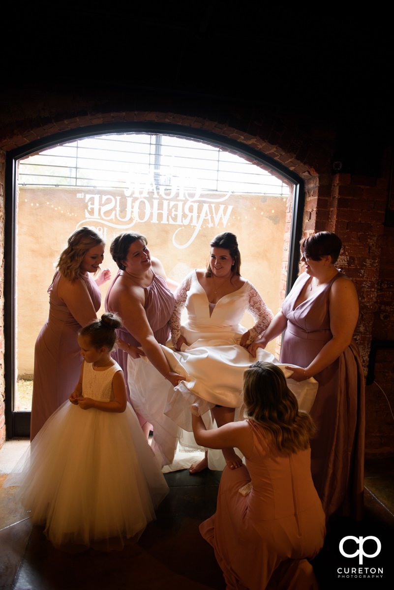 Bridesmaids helping the bride into her dress before the ceremony at The Old Cigar Warehouse.