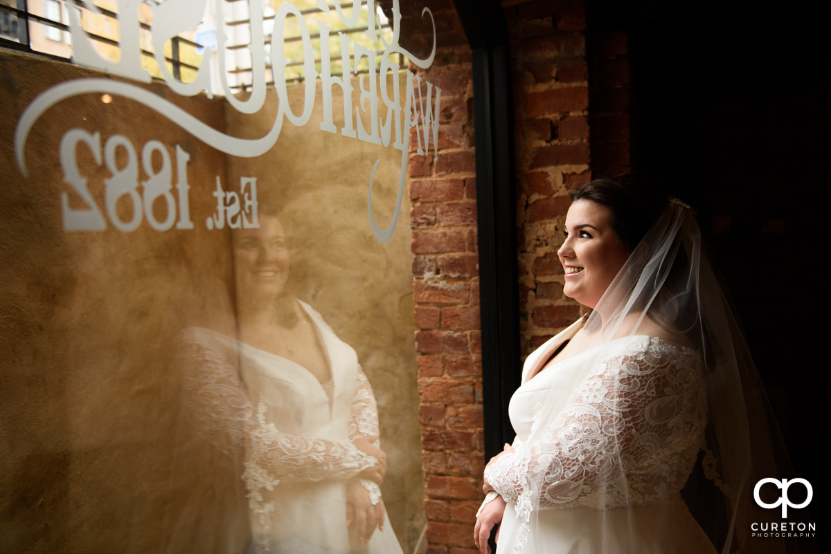 Bride looking out the window at The Old Cigar Warehouse.