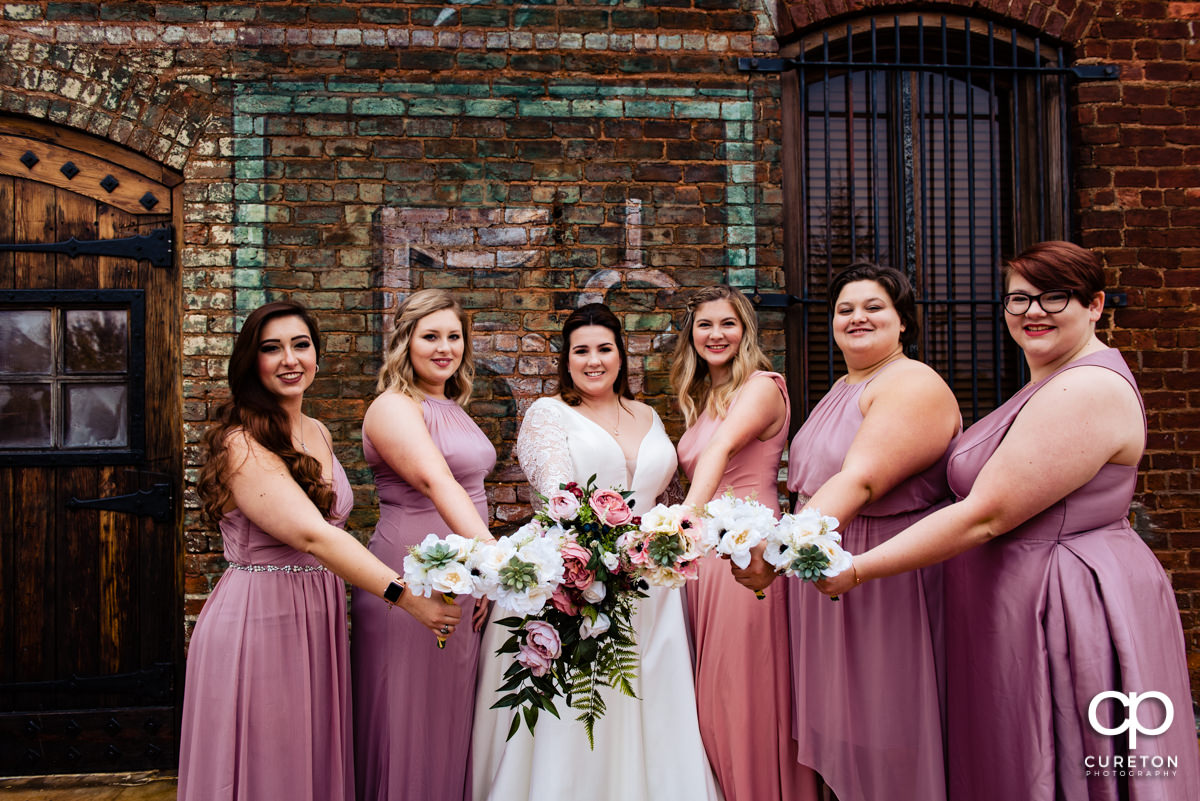 Bride and bridesmaids showing off their flowers.